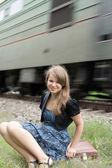Dziewczyna siedzi na walizkę — Zdjęcie stockowe