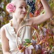 Beautiful girl in a long skirt with a basket of grapes — Stock Photo
