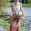 Stock Photo: Beautiful girl in a long skirt with a basket of grapes