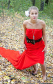 Pretty girl in red dress in the autumn in the woods — Stock Photo
