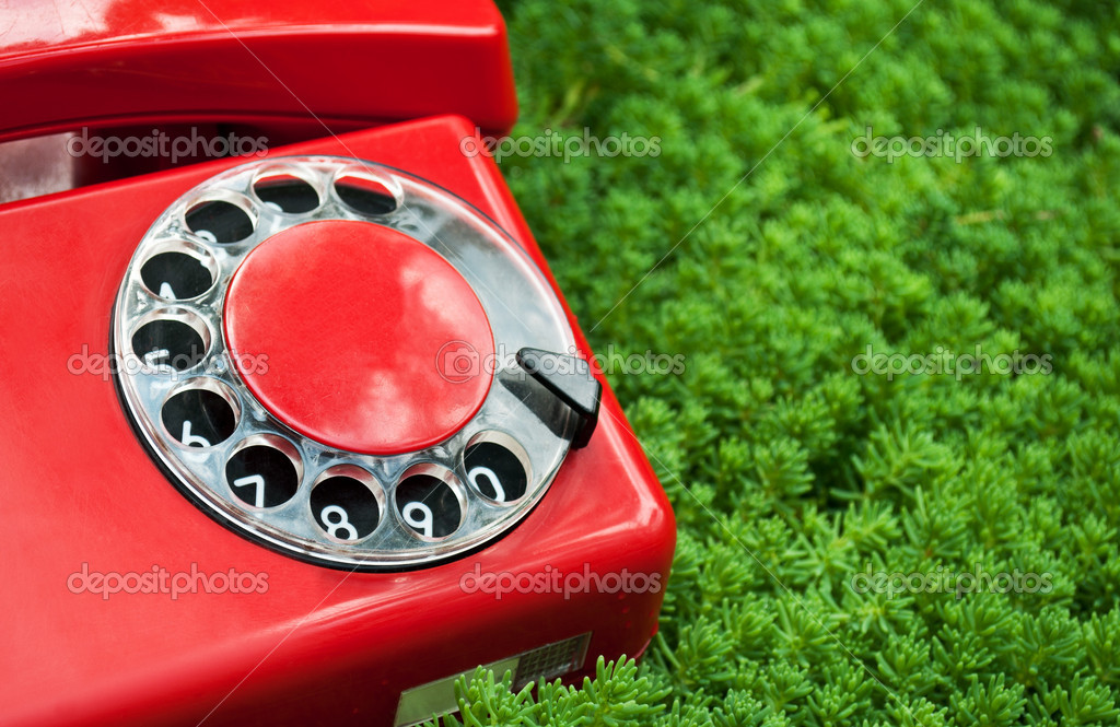 Red and old telephone on a green grass background — Stock Photo #6821174