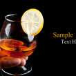 Cognac with lemon in hand — Stock Photo