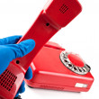Man in blue gloves picked it up the red phone — Stock Photo