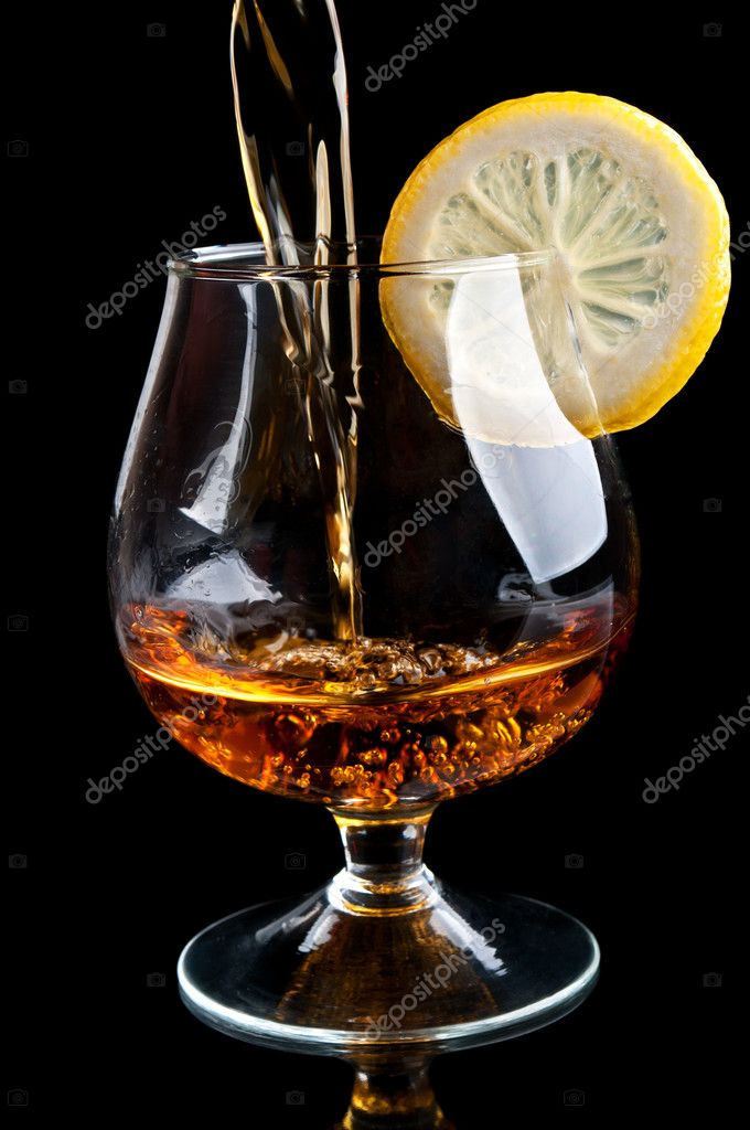 Cognac with lemon in a classic glass isolated on a black background  Stock Photo #6836561
