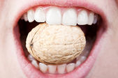 Woman eating hard nut — Stock Photo