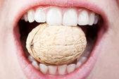Woman eating hard nut — Stock Photo