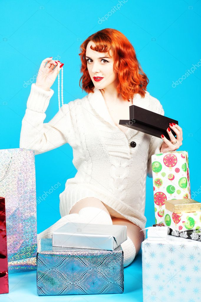 Redhead woman on a blue background opening her Christmas presents  Stock Photo #7826002