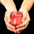 Red gift box with hands — Stock Photo