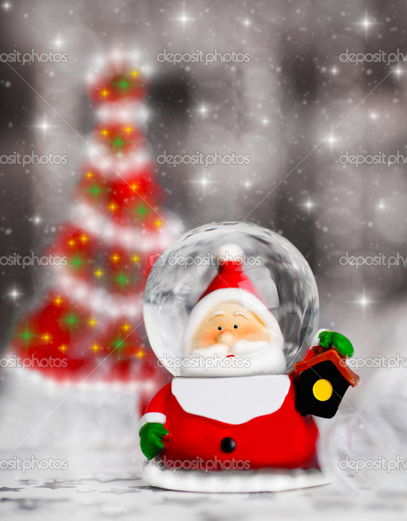 Snow globe Santa Claus, Christmas tree decoration, traditional winter holiday ornament  with shiny blur lights background, selective focus  Stock Photo #7580674