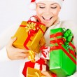 Happy Santa girl holding gifts — Stock Photo