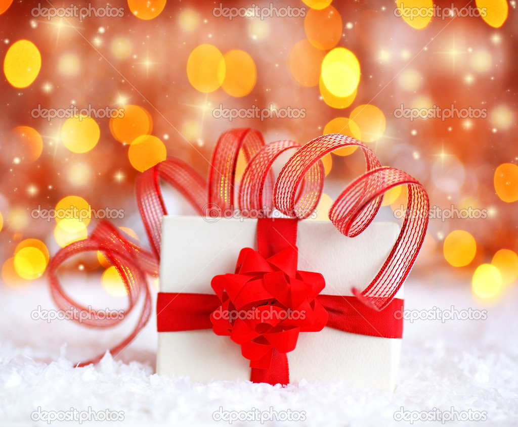 Warm holiday background with white present gift box wrapped with red ribbon & bow, Christmas ornament and new year decoration over defocus lights — Stock Photo #7790110