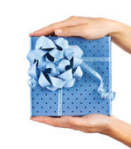 Female hands holding blue gift box — Stock Photo