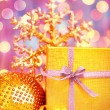 Golden Christmas gift with baubles decorations — Stock Photo