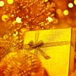 Golden Christmas gift with baubles decorations — Stock Photo #7939527