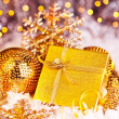 Golden Christmas gift with baubles decorations and candles — Stock Photo #7939596