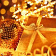 Golden Christmas gift with baubles decorations — Stock Photo #7939608