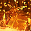 Golden Christmas gift with baubles decorations and candles - Stok fotoğraf