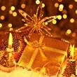 Golden Christmas gift with baubles decorations and candles - Stockfoto