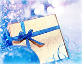 Golden blue Christmas gift with baubles decorations — Stock Photo