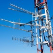 Antenna repeater messy mast in blue sky - Stock Photo