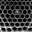 Gray PVC tubes plastic pipes stacked in rows - Stock Photo