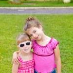Children girls hug in green grass park — Stock Photo #6947276