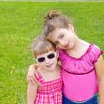 Children girls hug in green grass park — Stock Photo #6947290