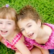Children girls laughing sit on green grass — Stock Photo #6947427