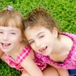 Children girls laughing sit on green grass — Stock Photo