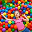 Child girl on colorful balls playground high view - Stock Photo