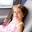 图库照片: Child little girl indoor car putting safety belt