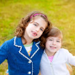 Happy sister girls in winter park grass playing — Stock Photo