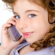 Blue eyes child girl talking mobile phone - Stock Photo