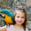 Blue eyes child girl with yellow parrot - Stock Photo