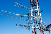Antenna repeater messy mast in blue sky — ストック写真