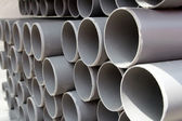 Gray PVC tubes plastic pipes stacked in rows — Stock Photo