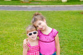 Children girls hug in green grass park — Stock Photo