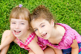 Children girls laughing sit on green grass — Stock Photo