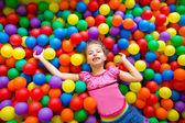 ребенок девочка на красочных шаров площадка высокое мнение — Стоковое фото