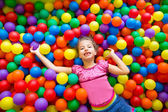 Child girl on colorful balls playground high view — Stock Photo
