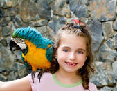 Blue eyes child girl with yellow parrot — Stock Photo