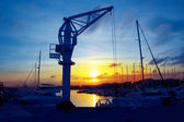 Boats crane at sunset in marina port of Salou — Stock Photo
