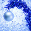 Christmas silver bauble on blue winter ice - Stock Photo