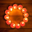 Candles cirlce shape on warm golden wood - Stok fotoğraf