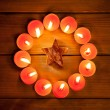 Chirstmas candles circle over wood and symbol — Foto de Stock