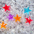 Christmas colorful glass stars on cold ice — Stock Photo