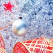 Christmas silver bauble and red ribbon on ice — Stock Photo