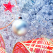 Christmas silver bauble and red ribbon on ice — Stock Photo #7002899