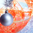 Christmas silver bauble with red ribbon on ice — Stock Photo