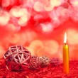 Christmas candles with dried baubles on red - Stock Photo